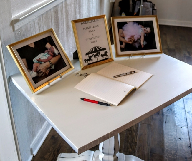 Gold framed monthly photos and Carousel themed notebook for guests to write 1st birthday wishes