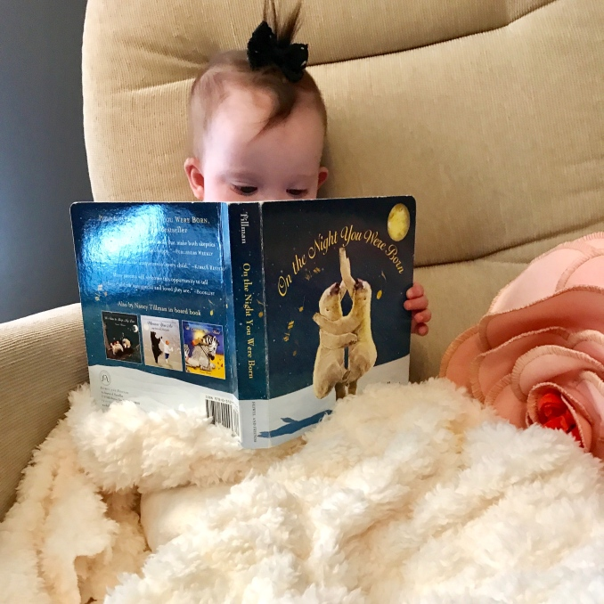 Kara holding one of her favorite books, On The Night You Were Born by Nancy Tillman